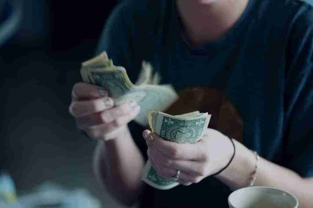 Parents Ask For Money. A Woman counting dollars bills.